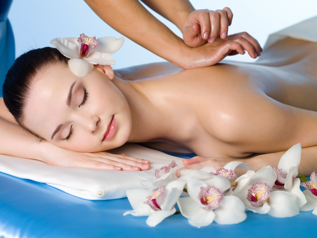 Relaxing massage of back for young beautiful woman in spa salon - horizontal